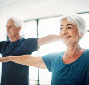 An Elderly Couple Holds Their Arms Outwards From Their Sides In A Yoga Pose.