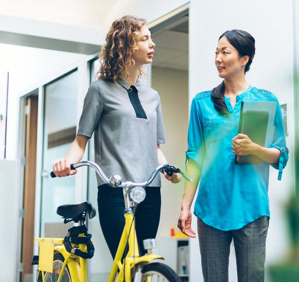 A Middle-Aged Woman Holding A Yellow Bike Talks To A Female Middle-Aged Doctor.