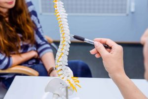 Closeup medical doctor woman pointing on spine model and explaining female patient her problem. Healthcare concept.
