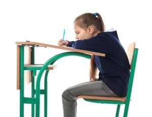 Incorrect posture concept. Little girl sitting at school desk on white background