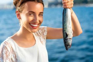 Young woman holding fresh fish outdoors on sea background