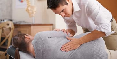 Shot of a chiropractor adjusting a young woman's spine